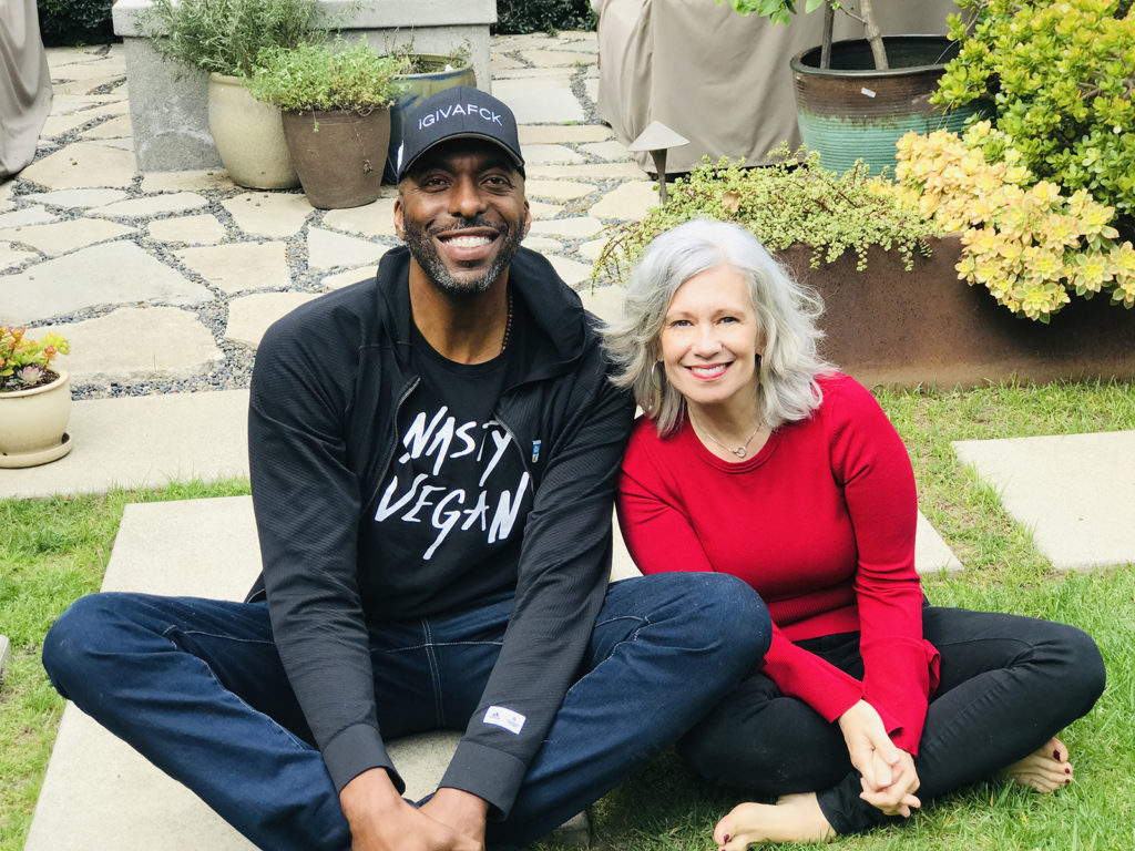 John Salley and Elysabeth Alfano sitting on the ground